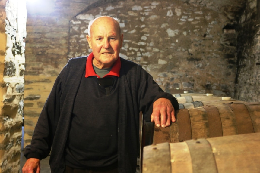 A older man wearing a red shirt under black robes, standing next to some wine barrels.