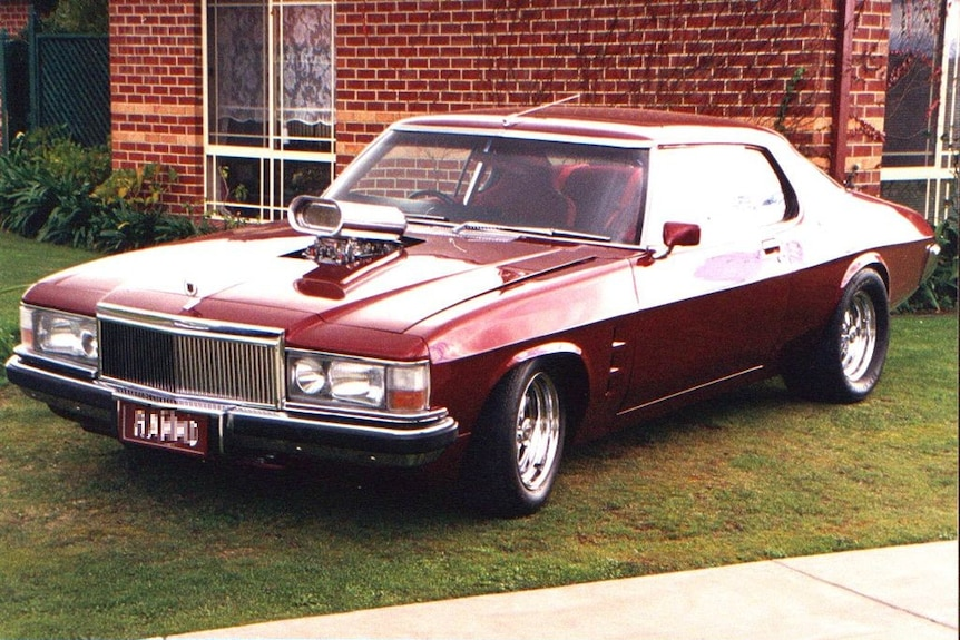 A maroon Holden Monaro classic car parked on grass in front of a red brick house