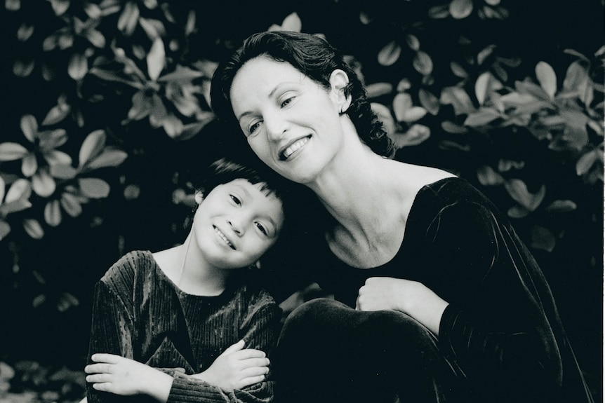 A black and white image of a mother and her daughter, both in ballet tights