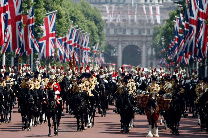 Formally dressed soldiers sit atop of horses in a parade lined with British flags