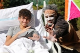 A young boy in a hospital bed holds his hands towards the camera next to an aboriginal man with face paint.