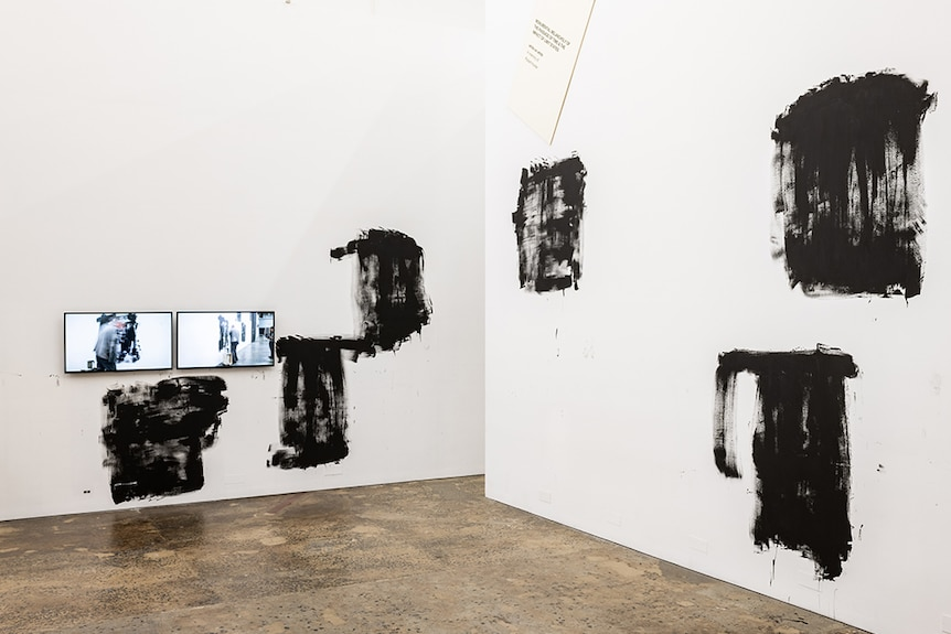 Two side by side tv screens showing Mike Parr performance hang near various roughly painted black squares on white gallery wall.