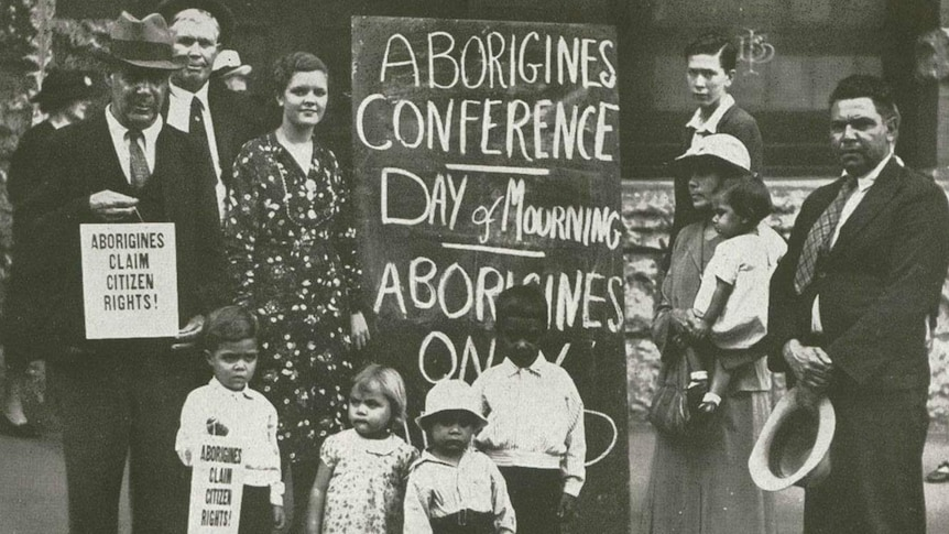 """Indigenous protesters gather around a placard  that reads """"Aborigines conference - day of mourning"""""""
