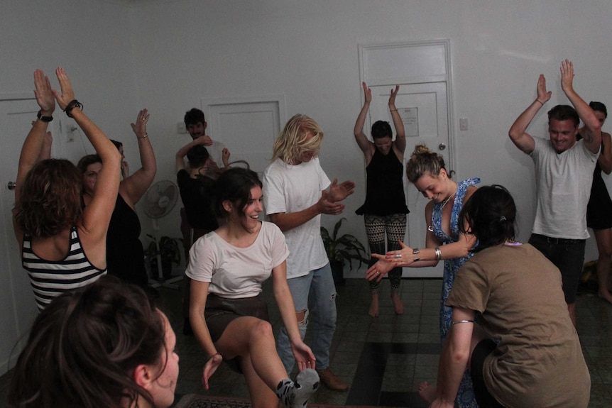 People dance freely around a large white room in Brisbane while letting go of their inhibitions