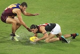 Two AFL players contest for the ball in wet conditions at the Gabba in Brisbane.
