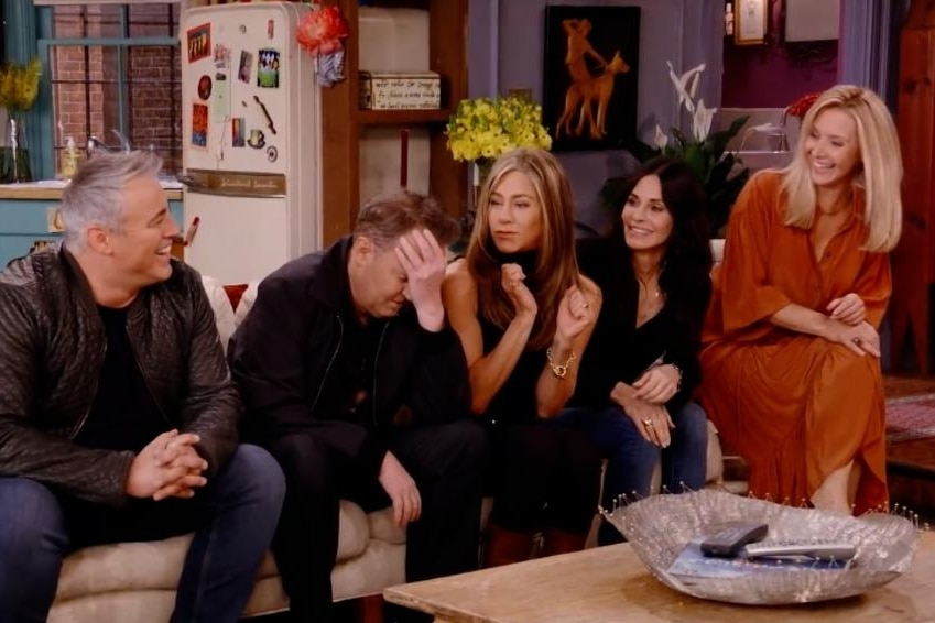Five people sit on a couch in an apartment, laughing, and Chandler has his head in his hands