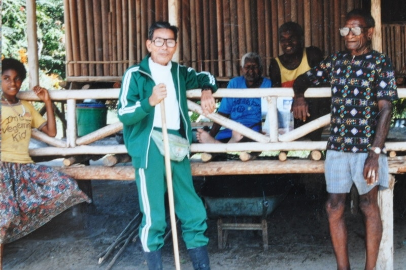 An old photo of Kokichi Nishimura with PNG villagers