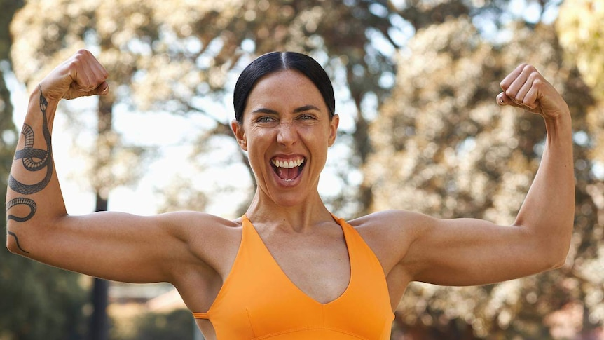 A woman in an orange exercise top flexes with both arms and smiles at the camera with a tattoo on her torso