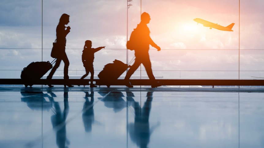 Silhouettes of a family walk past an airport window as a plane takes off outside.