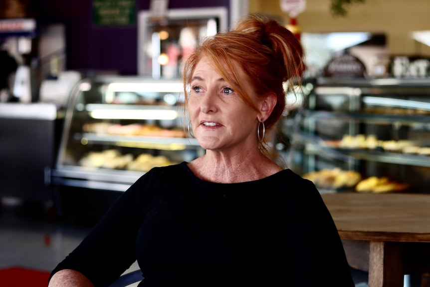 A lady in a black top looks of camera, with counters of baked goods behind her