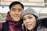 A selfie of a man and woman at a Japanese train station.