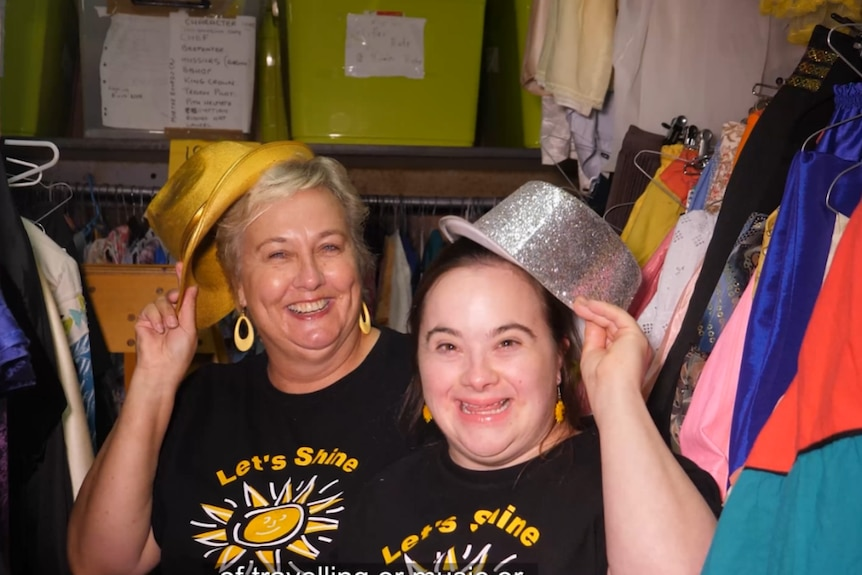 Two smiling ladies hold up sparkly bowler hats and look at the camera.