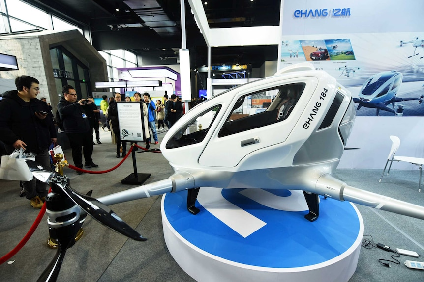 A white passenger drone is on display behind a red rope and a crowd looks at it and takes pictures.