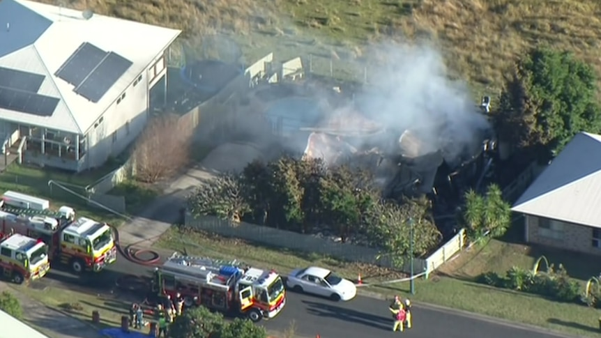 An aerial image of the remains of a house obscured by smoke. A number of fire engines are parked on the street outside.