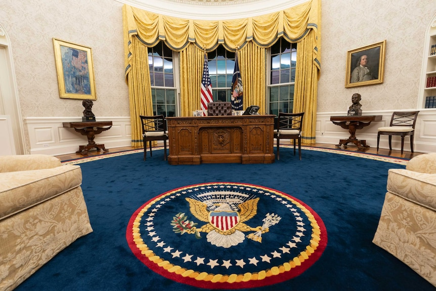 A wide photo of the Oval Office, including a blue rug, gold curtains and the Resolute Desk.
