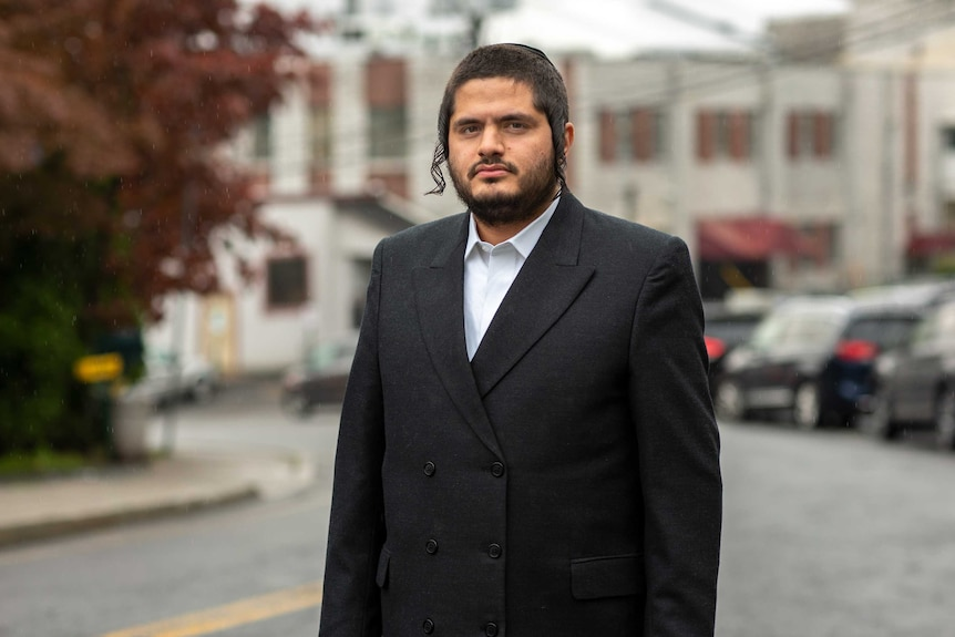 A man in a suit and skull cap stands on a suburban US street