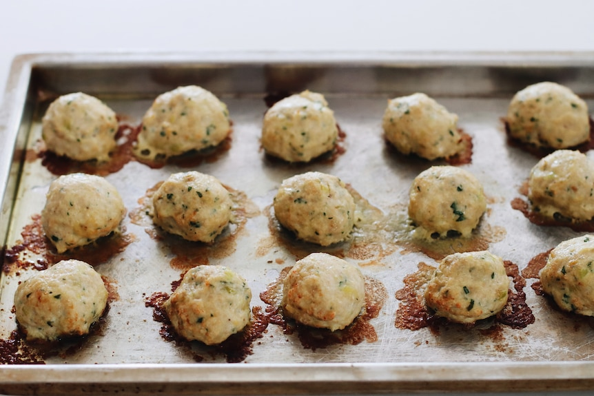 A tray of just-baked chicken, leek and parmesan meatballs, a family dinner.