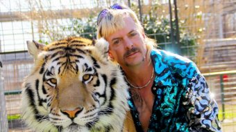 A picture of a blond man with a moustache and sparkly top with a tiger.