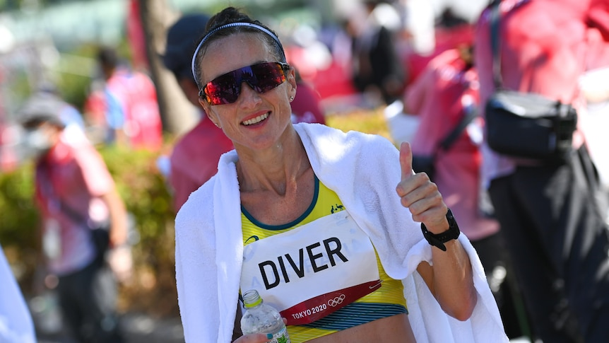 A smiling Australian athlete gives a thumbs up as she is wrapped in an ice towel after the women's marathon.