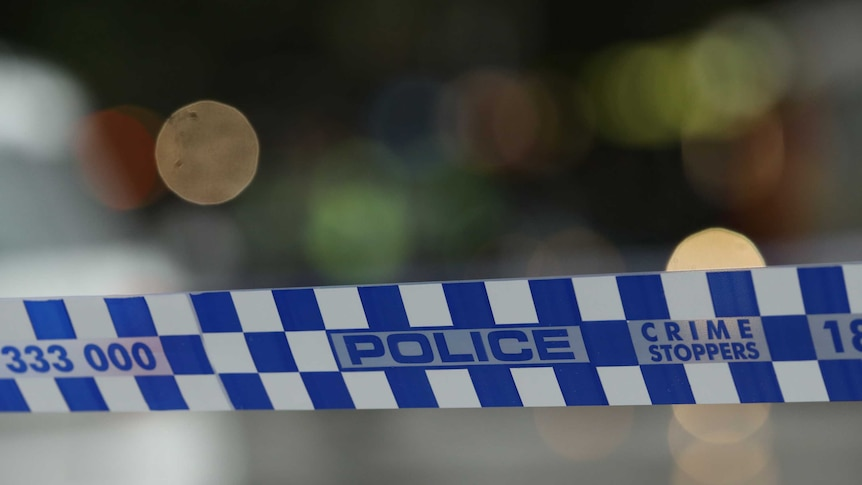 Photograph of blue-and-white Australian police tape, with an out-of-focus background.