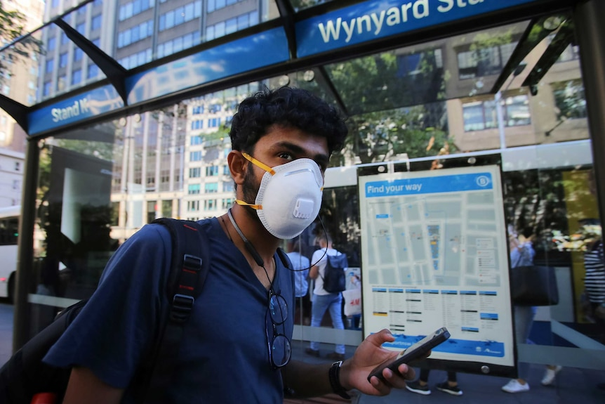 A man wears a face mask as he waits for a bus in Sydney.