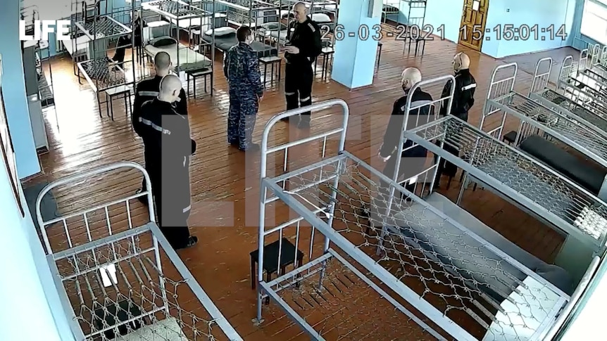 Security camera footage shows a man surrounded by guards and beds without mattresses in a prison.