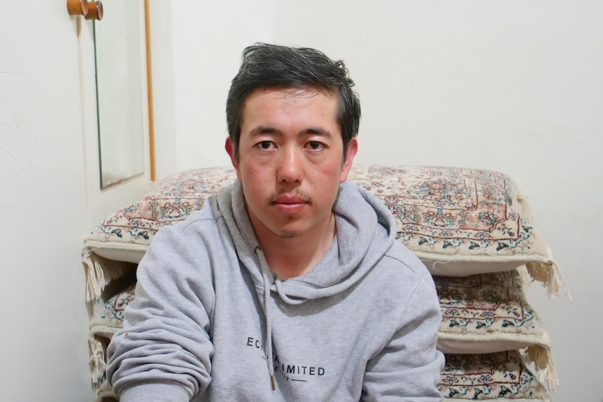 Man sits on floor wearing a grey hoodie staring straight at camera