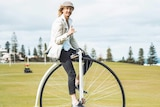 A young man riding a penny-farthing bicycle