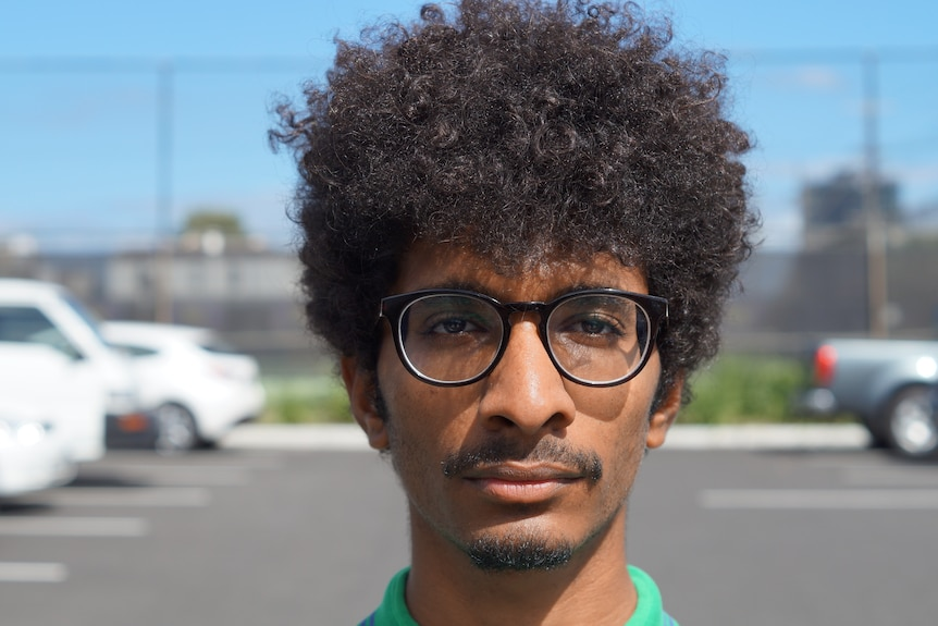 Man with an afro and black rimmed glasses