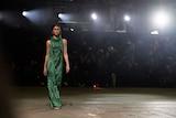 A model in a green woven dress walks a runway.