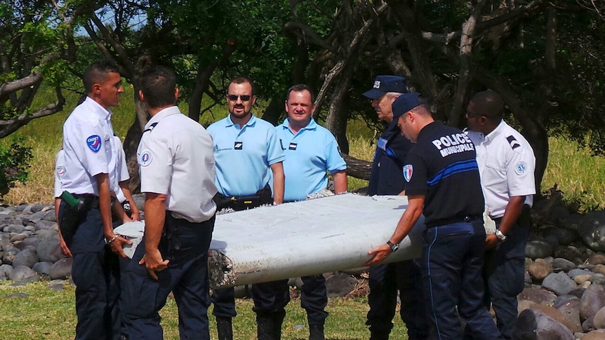 French gendarmes and police carry a large piece of plane debris