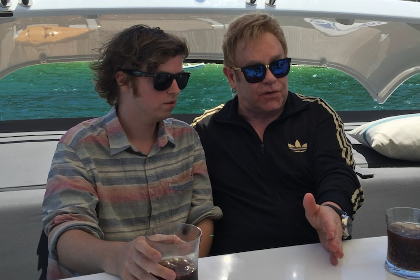 An older man in sunglasses sitting on a yacht and talking with a younger man who is also wearing sunglasses.