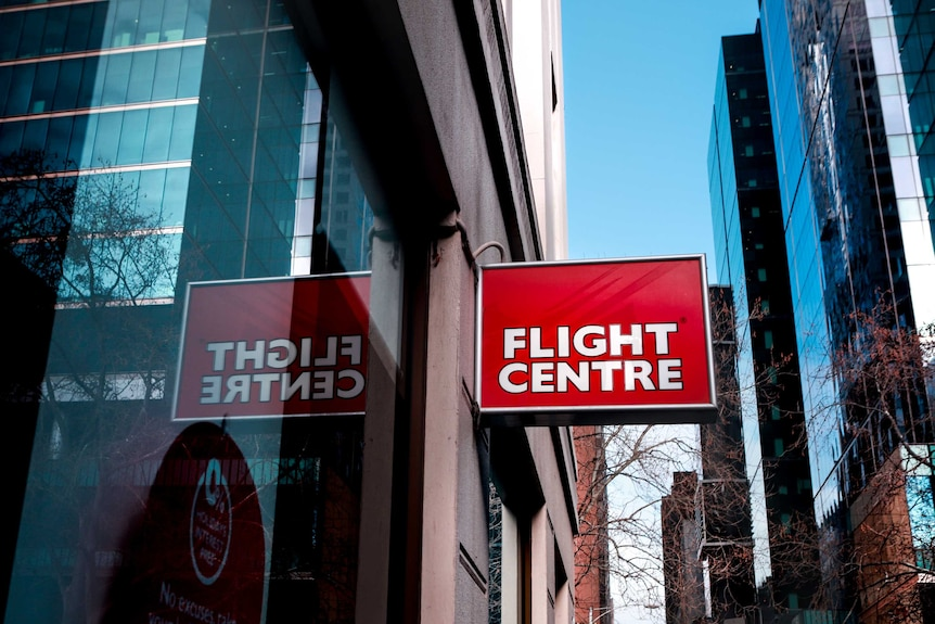 A red and white Flight Centre sign in the foreground, with the Melbourne CBD skyline in the back.