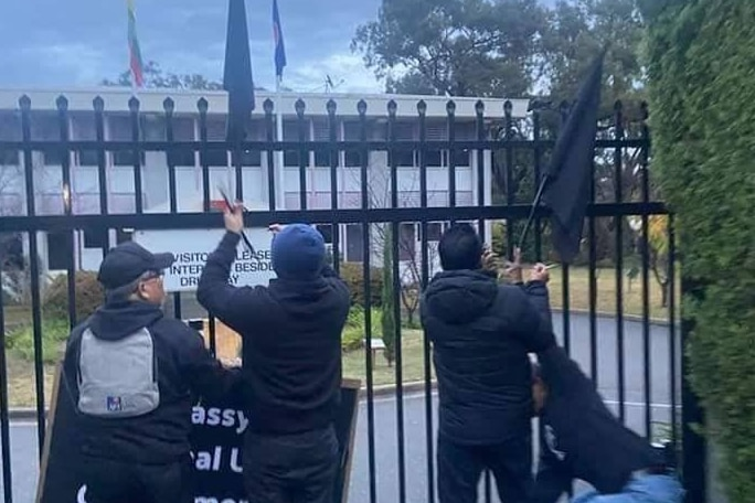 Three protesters with flags try to attach flags to the gate at the Myanmar embassy in Canberra.