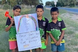 Three boys hold up signs beside a road
