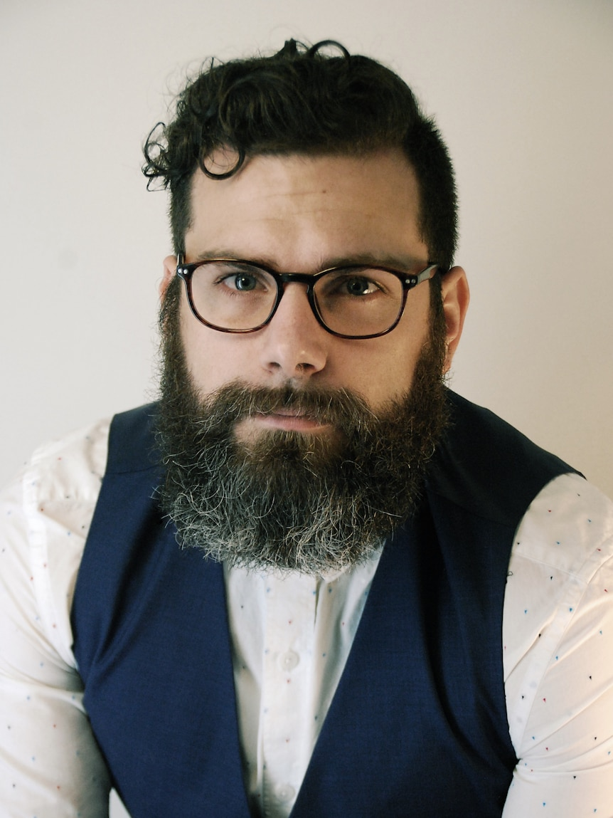 A portrait of a man wearing a white shirt and a blue vest with dark hair, glasses and a beard.