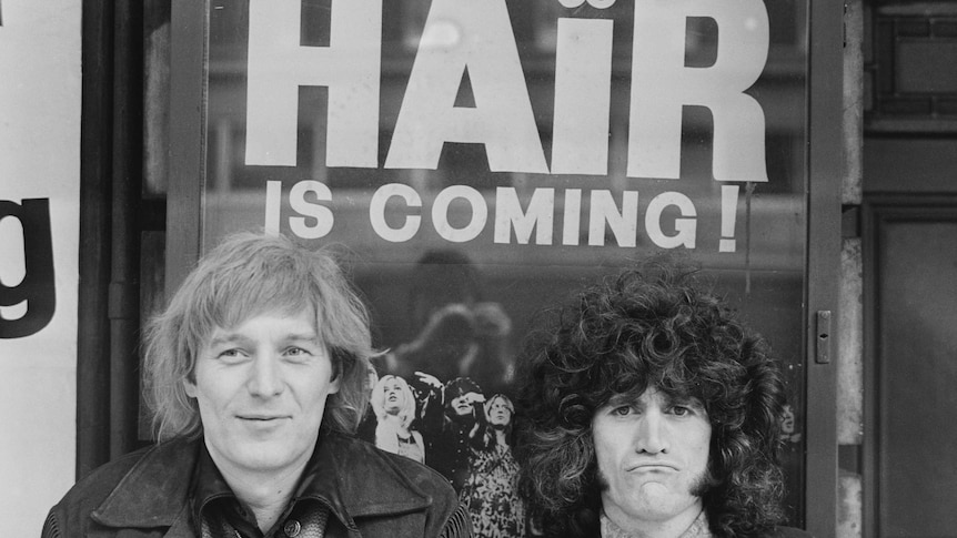 """A black and white photo of two men in 1968, the poster in the background says """"Hair is coming!"""""""