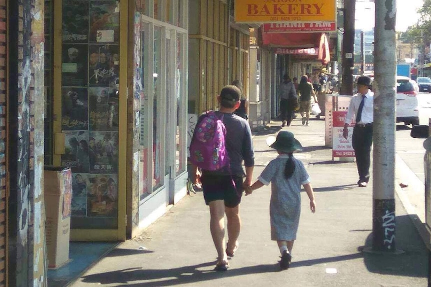 A man walks with a girl along Victoria Street in Richmond.
