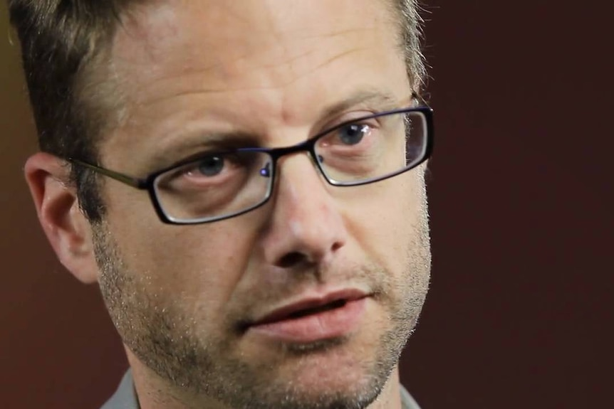 A man with glasses looks forward, his head tilted slightly