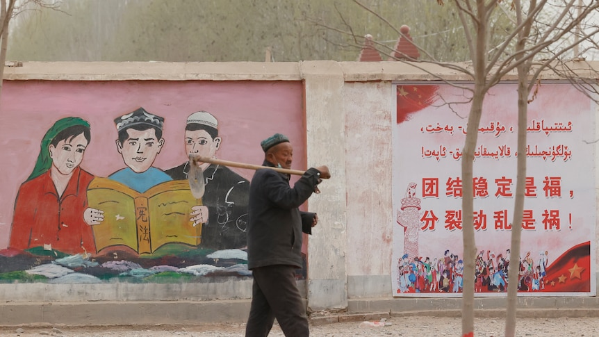 A farmer walks past propaganda depicting ethnic minority residents reading the Chinese constitution