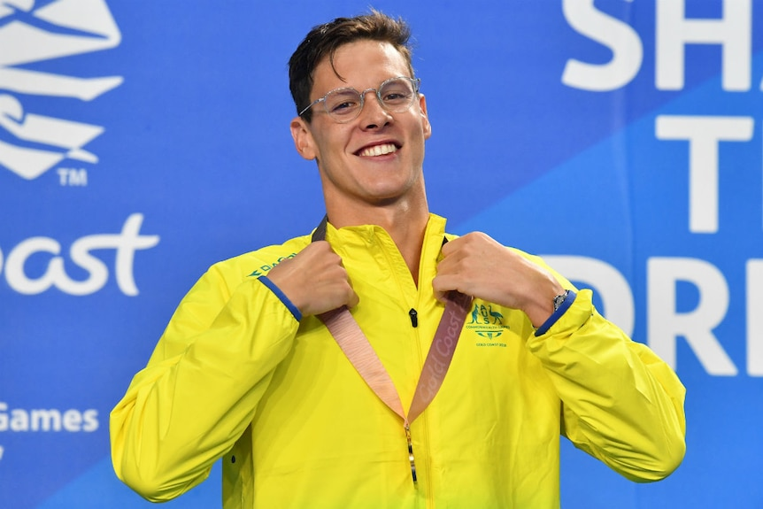 Mitch Larkin stands on the podium, smiling and wearing a Gold Medal.