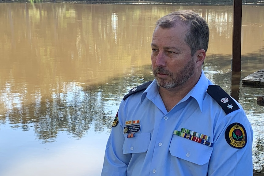 Man in blue shirt stand in front of a flooded BBQ shed