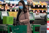a woman wearing a mask carrying a shopping basket inside a grocery store