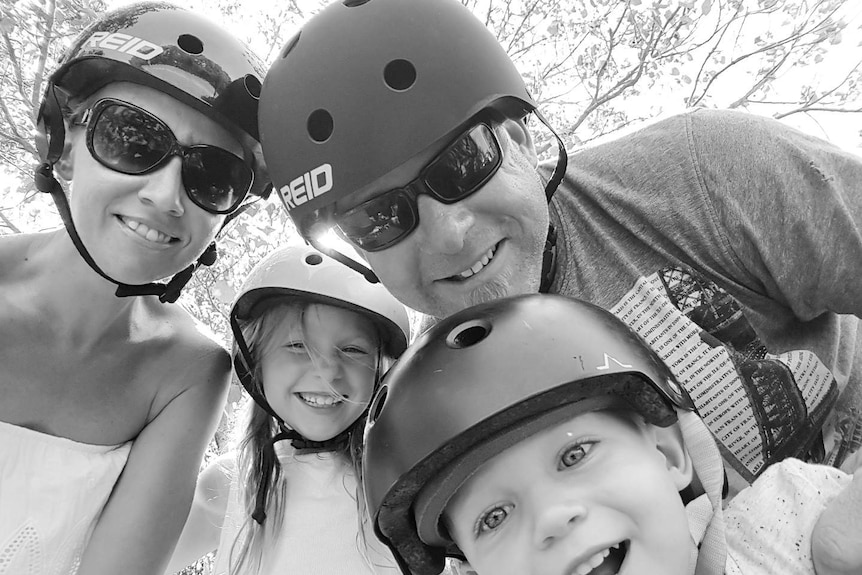 Black and white photo of Aaron Cox and his wife Bindi and two children wearing helmets.