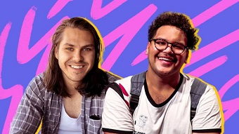 Two young men, Ethan on the left has long hair, Bromley on the right is wearing glasses. They are smiling.