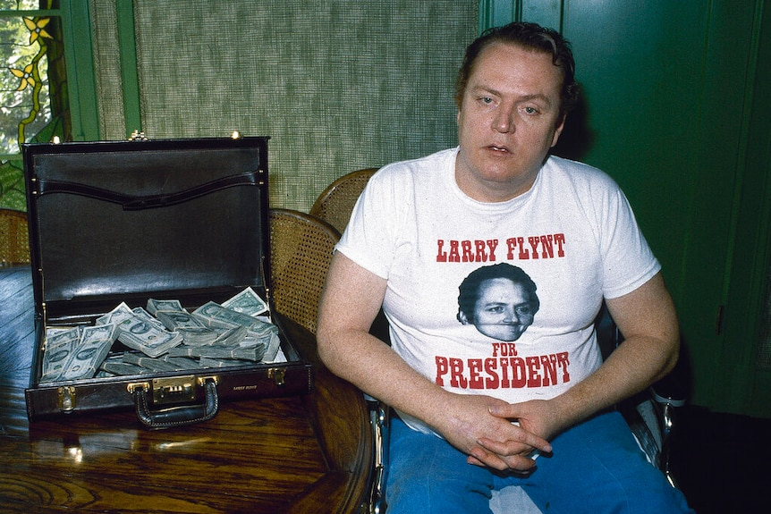 """A man wearing a t-shirt which says """"Larry Flynt for President"""" sits in a wheelchair next to a briefcase of cash."""