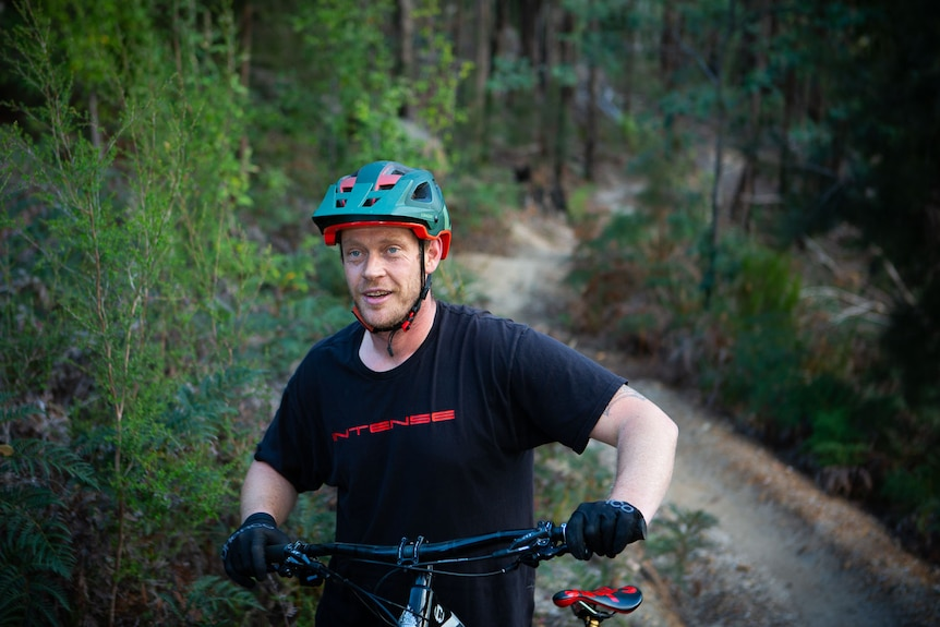 A mountain bike rider standing next to his bike, trail winds off into the forest behind.