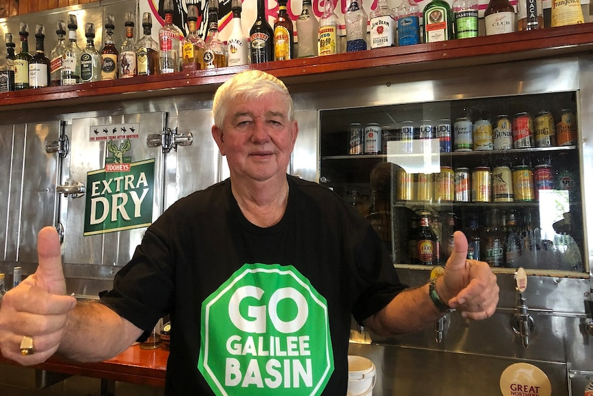 Pub owner Leslie Boal in Clermont wears a pro-Adani shirt and gives the thumbs up.