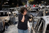 A woman reacts as she tries to find her dog, following a wildfire at the village of Mati.