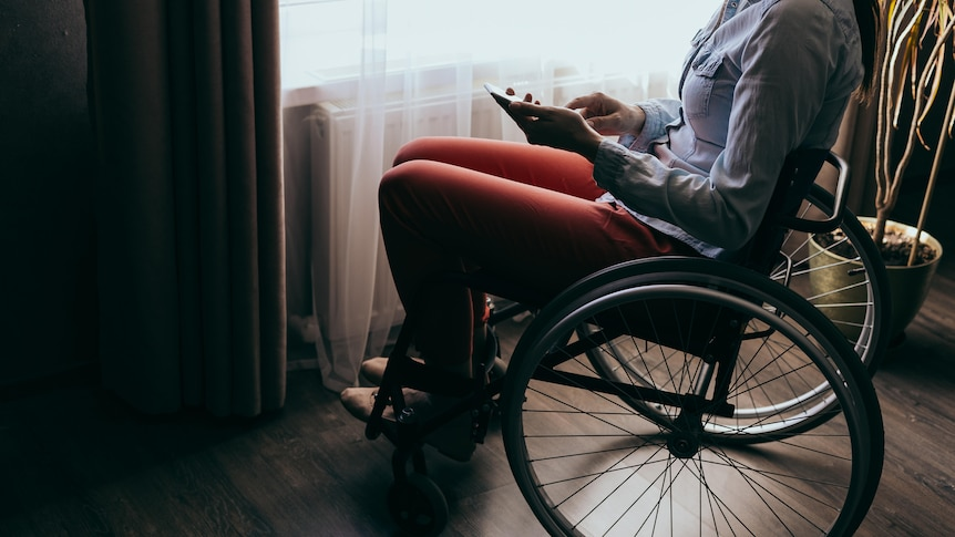 A young woman sitting in a wheelchair by a window is using a smartphone, the lighting in the room is shadowy and dark.